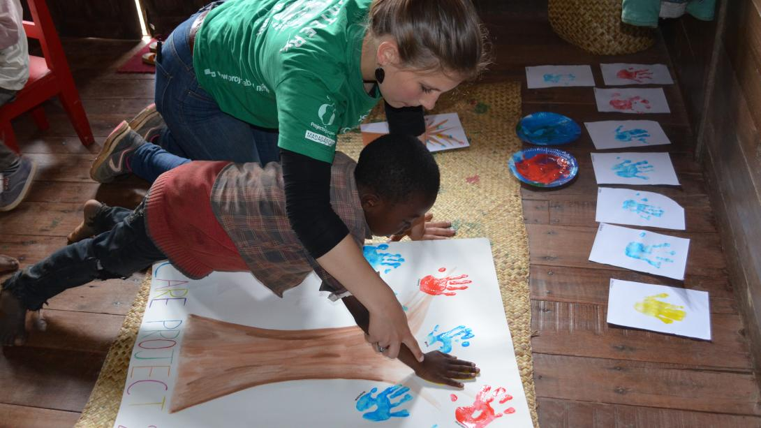 On a mission trip to Africa for high school students, a volunteer helps a child on an art project.